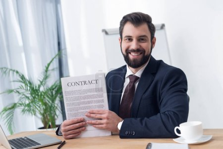 portrait of smiling businessman with contract at workplace in office
