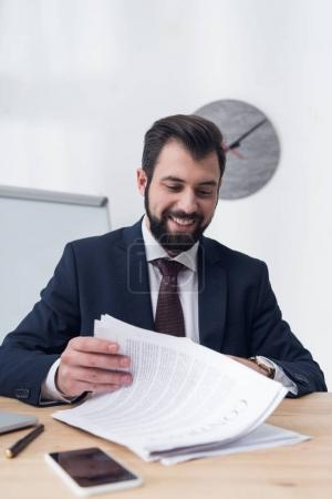 smiling businessman with contract sitting at workplace in office