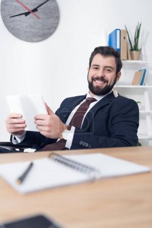 Photo pour Portrait d'homme d'affaires gai avec tablette sur lieu de travail au bureau - image libre de droit