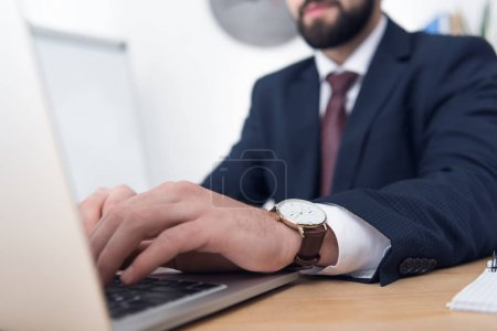 partial view of businessman in suit typing on laptop