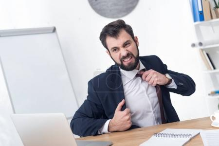 portrait of angry businessman looking at laptop screen at workplace in office