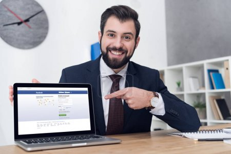 portrait of smiling businessman pointing at laptop at table in office