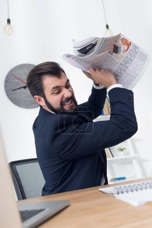 Photo for Portrait of angry businessman throwing newspaper at workplace - Royalty Free Image