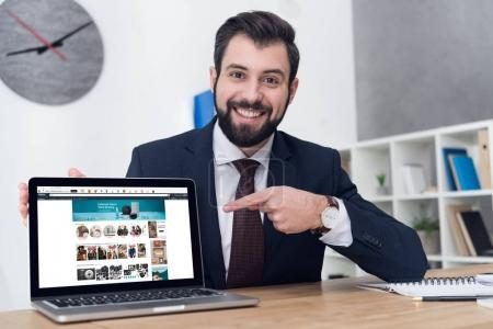 portrait of young businessman pointing at laptop at workplace in office