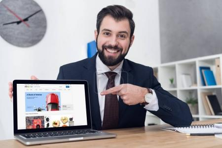 portrait of cheerful businessman pointing at laptop at workplace in office
