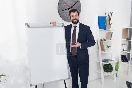 Photo for Smiling businessman pointing at empty white board in office - Royalty Free Image