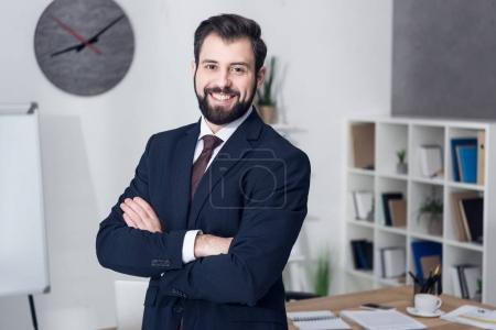 portrait of smiling businessman with arms crossed in office