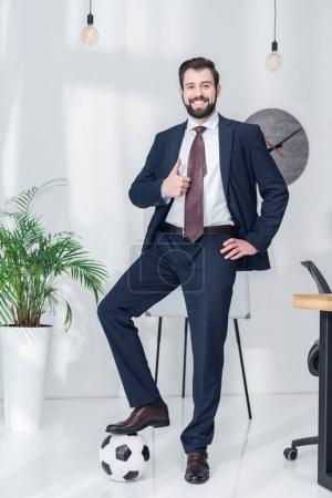 cheerful businessman standing with one leg on soccer ball and showing thumb up in office