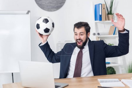 excited businessman in suit with soccer ball looking at laptop screen at workplace in office
