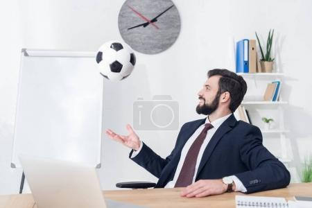 businessman in suit throwing soccer ball at workplace in office