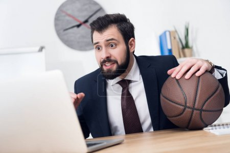 excited businessman with basketball ball at workplace in office