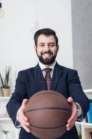selective focus of smiling businessman showing basketball ball in hands in office
