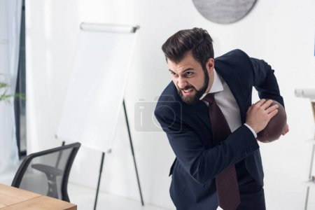side view of angry businessman in suit playing rugby in office