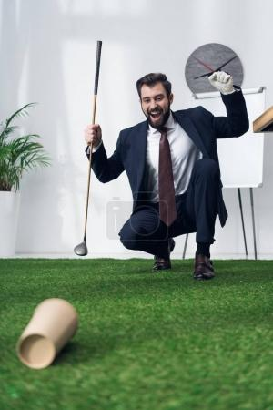 excited young businessman playing golf in office