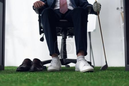 partial view of businessman with golf equipment  in office