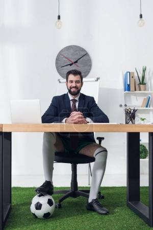 smiling businessman with soccer ball sitting at workplace in office
