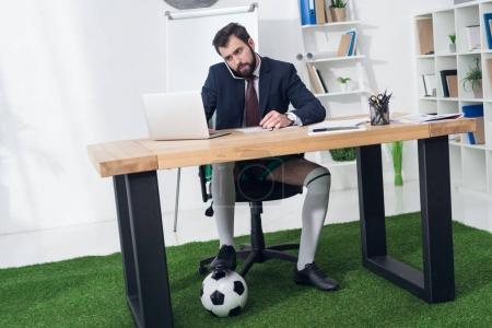 businessman with soccer ball talking on smartphone at workplace in office