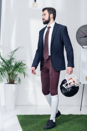 young businessman with rugby helmet in office