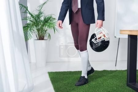 cropped shot of businessman with rugby helmet in hands in office