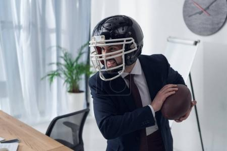 young furious businessman in helmet playing rugby in office