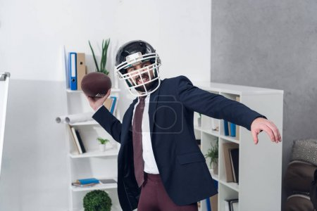 portrait of young furious businessman in helmet playing rugby in office
