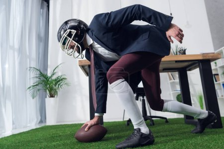 side view of businessman in rugby helmet playing american football in office