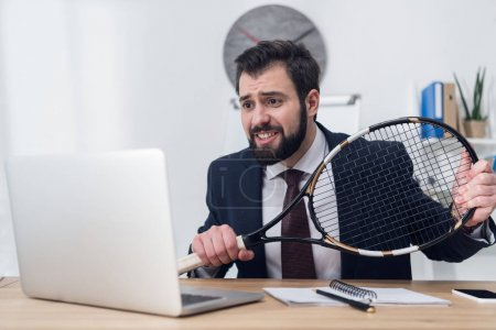 businessman in suit with tennis racket at workplace