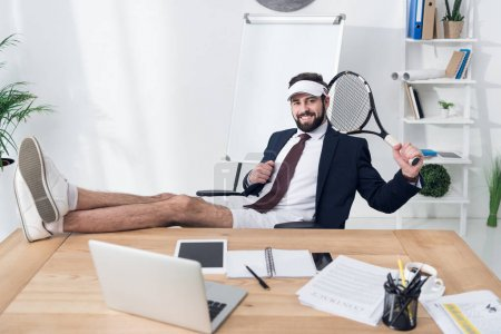 young businessman in cap with tennis racket resting at workplace in office