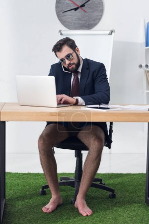 Photo for Businessman in jacket and shorts talking on smartphone at workplace - Royalty Free Image