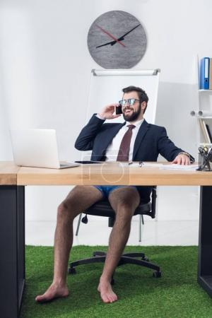businessman in jacket and shorts talking on smartphone at workplace with laptop