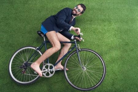overhead view of businessman riding bicycle on green lawn