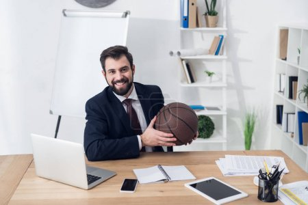 portrait of young businessman with basketball ball at workplace in office
