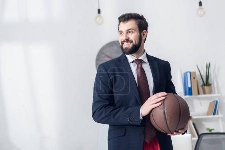 Photo for Portrait of businessman in jacket holding basketball ball in office - Royalty Free Image