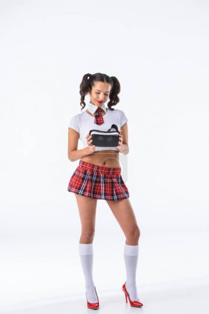 smiling sexy schoolgirl holding vr headset isolated on white