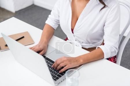 cropped shot of attractive woman in unbuttoned shirt using laptop