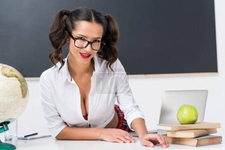 young sexy teacher sitting at workdesk in front of blackboard
