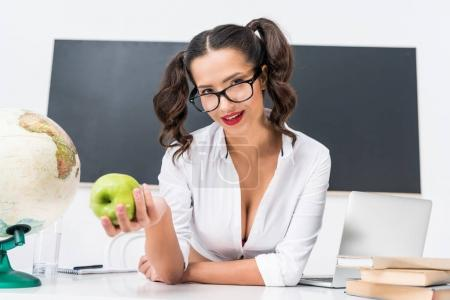 Photo for Young sexy teacher with green apple sitting at workplace in class - Royalty Free Image