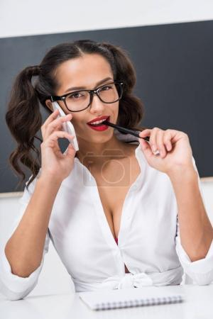 young sexy schoolgirl in unbuttoned shirt with ponytails talking by phone in classroom