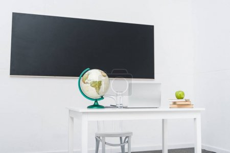 Photo for Teachers desk in classroom in front of chalkboard - Royalty Free Image