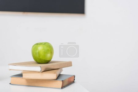 green apple on stacked books at classroom