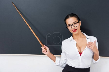 young seductive teacher pointing at chalkboard