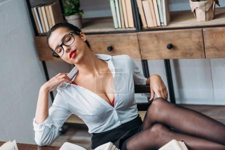 hot young teacher in unbuttoned shirt sitting at library