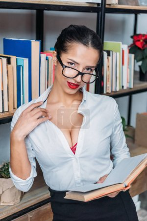 young sexy teacher readin book at library while leaning on bookshelves