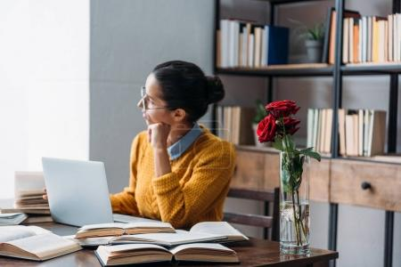 young student girl preparing for exam at library with red roses in vase