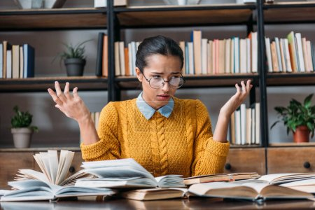 bewildered young student girl preparing for exam at library