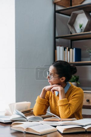 thoughtful young student girl preparing for exam at library and looking at window