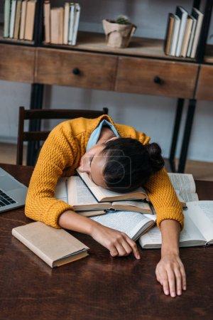 jeune fille étudiant surmené, dormir la bibliothèque tout en préparant l'examen à la bibliothèque