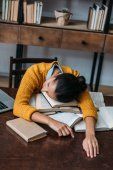 overworked student girl sleeping at library while preparing for exam at library