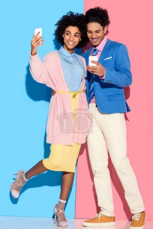 Young african amercian girl taking selfie and hugging stylish guy who looks at his phone on pink and blue background