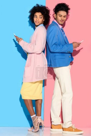 Young african amercian smiling couple with phones standing back to back  on pink and blue background